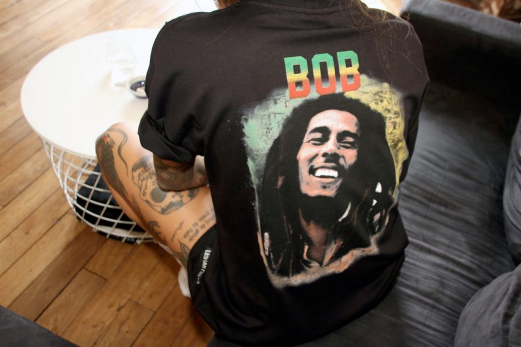 The tee shirt has a boxy fit with a print on the back. The name is in rasta colors and the numbers are replaced by the portrait of the legend.